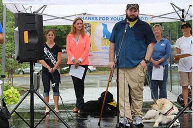 "Capt. Gavin White (U.S. Army) and his assistance dog Stuart address the crowd at the Canine Companions for Independence DogFest Walk 'n Roll on Sept. 12 in Arlington. Also pictured (from left) are 2015 Miss Maryland USA Amber Schroen; Honorary Event Chair Dr. Katy Nelson of ""The Pet Show with Dr. Katy;"" Canine Companions Northeast Region Executive Director Debra Dougherty; and DogFest Co-Chair Laura Clark."
