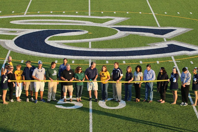 Community leaders, faculty and students gather to cut the ribbon formally dedicating the new artificial turf competition field at South County High School.