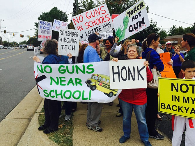 Protesters outside NOVA Firearms in McLean on Saturday, Sept. 26. The gun store is located on property that is adjacent to Franklin Sherman Elementary School.
