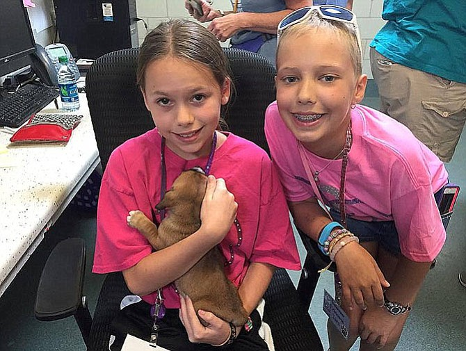 From left are Shelby Mysel and Tara Sankner with a puppy at the shelter.