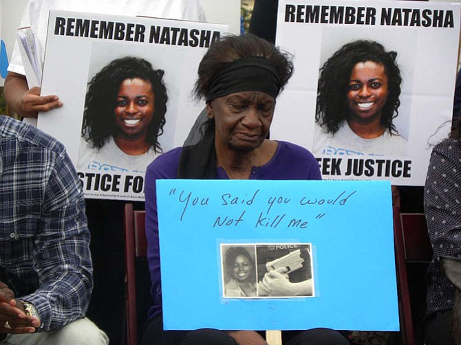 Natasha McKenna's great aunt Eudora Paul carries a sign with McKenna's words the day she was tasered by officers from the Fairfax County Sheriff's Department.