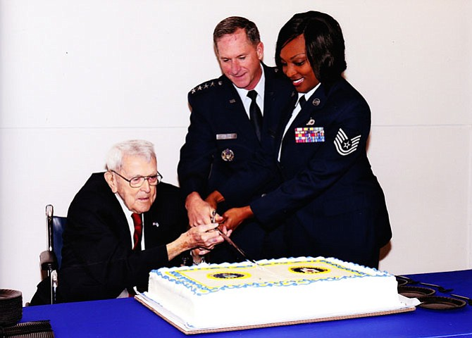 (From left) Col. Billy McLeod (retired) cuts the U.S. Air Force and Central Intelligence Agency birthday cake with Vice Chief of Staff of the U.S. Air Force Gen. David Goldfein and a young airman.