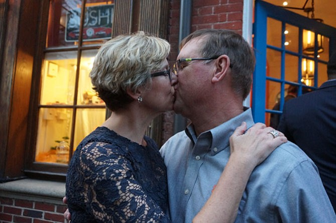 Rick and Elizabeth Myllenbeck share a celebratory kiss after the ribbon cutting at Sonoma Cellar at 207 King St.  in Old Town.