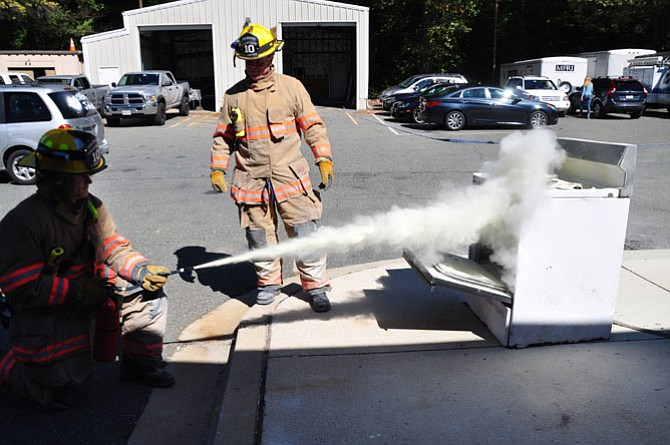 Firefighters Lukas and Greg Bastien extinguish a stove fire.
