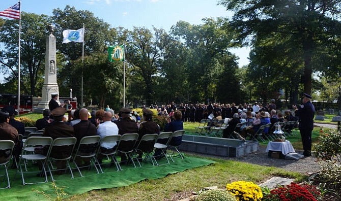 Fire Chief Robert Dube, at podium, leads a round of applause for Alexandria's firefighters and EMS first responders during the Oct. 9 ceremony at Ivy Hill Cemetery.
