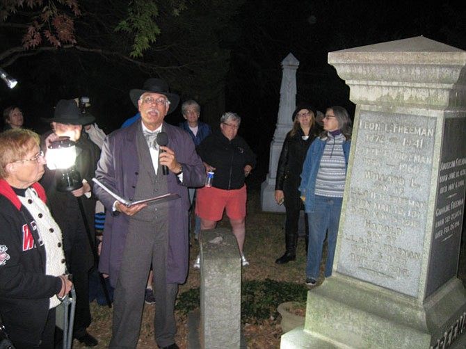 Jim Lewis next to the gravesite of Leon Freeman (1872-1941) buried at the Flint Hill Cemetery, during the Candlelight Cemetery Tour on Saturday night.