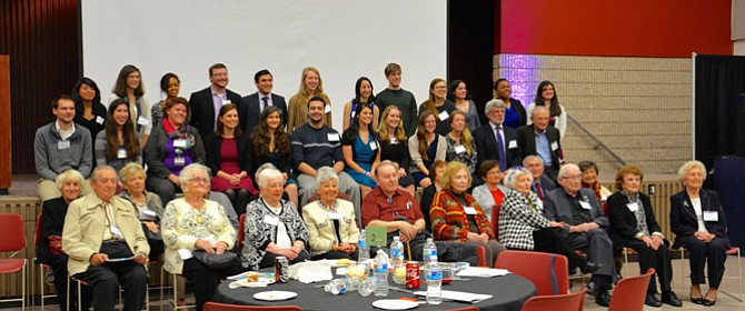 Taking the stage for a group photo with the honored guests Holocaust Survivors up front and the Students Ambassadors and members of Mason Hillel in the back at the third Expressions of the Holocaust: Memories event at George Mason University.