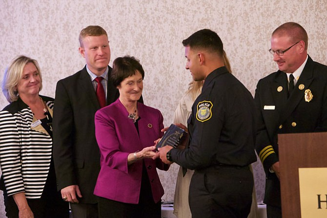 Fairfax Board of Supervisors Chairman Sharon Bulova smiles as she hands the Police Officer of the Year award to Officer Jackson Parker. Parker, of the Fort Belvoir Department of Public Safety, responded to a call from a mother who reported her son was locked in a bedroom, with a knife. He used his training to talk to the youth, diffuse the situation, and get the teen transported to a hospital where he could receive help.