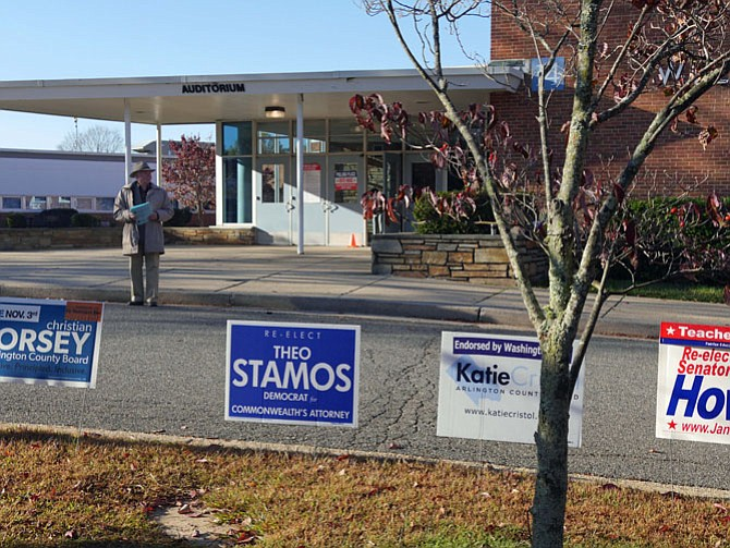 Signs line the curb for local candidates at Williamsburg Middle School polling place as a volunteer holds information for potential voters.