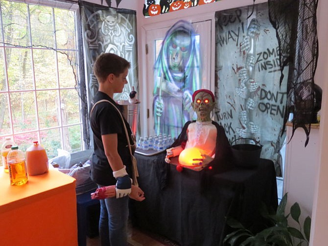 "Neighbor Robert Folsom, 11, helps Jim Harris put the finishing ""touches"" on the haunts."