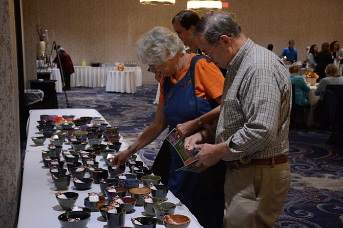 From left -- Fran and George of the Bryn Mawr area choose from handmade bowls at the Capital Area Food Bank Empty Bowls event held in Springfield on Oct. 29.