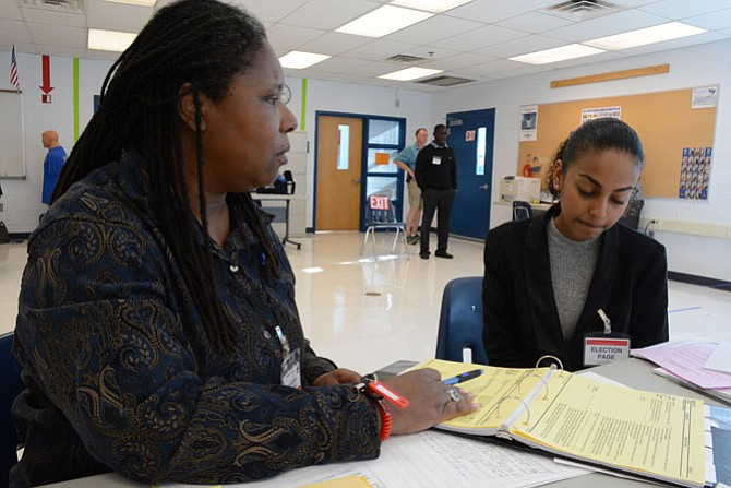 West Potomac High School chief election officer Doris McBryde of Mount Vernon (left) goes over polling location guidelines with election page Elham Mohaba (right) a sophomore at Thomas Edison High School.