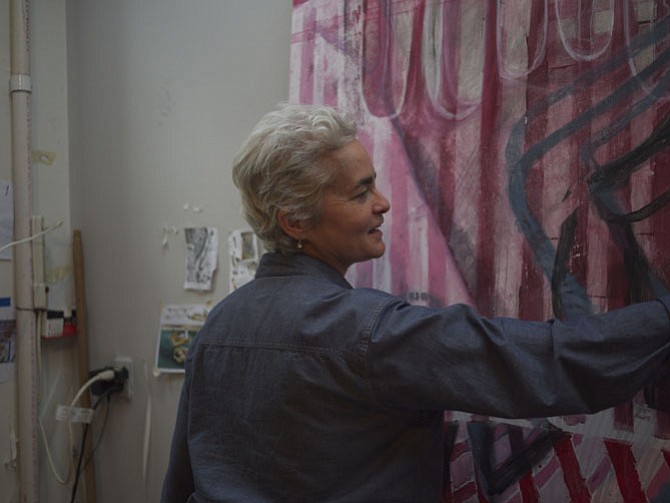 Sue Grace at work in her studio, with one of her paintings for upcoming exhibition.