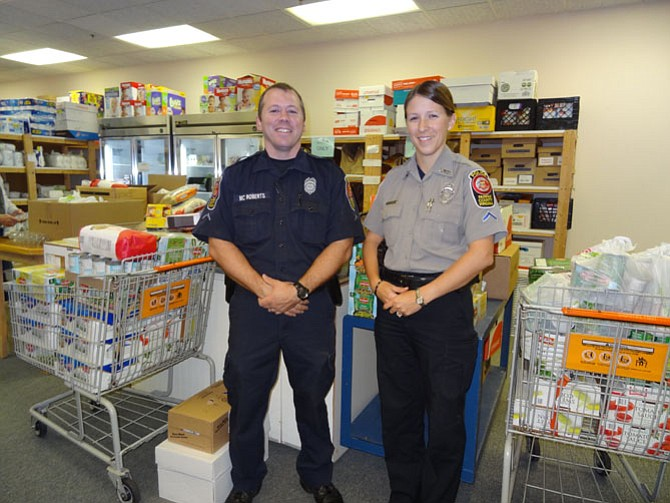 ully District Police Department, November 2014: PFC Tara Gerhard, Sully District Police Station food drive coordinator, and another officer deliver food to WFCM's pantry after sponsoring 30 families for Thanksgiving in 2014.