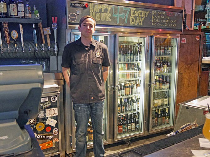 Will Bruder stands in front of the case of over 300 bottles of beer at Rustico's. He says they also offer 30 beers on tap with IPAs, Pilsners and Belgium Wits the most popular.
