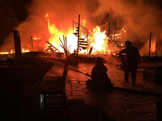 Firefighters attack the Great Falls blaze with hoses. The house was vacant and for sale.