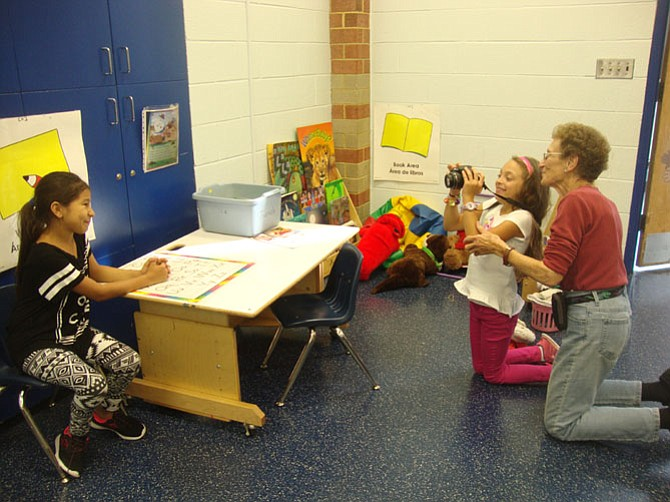 Nina Tisara helps students with photos for their author pages during a Family Legends class.