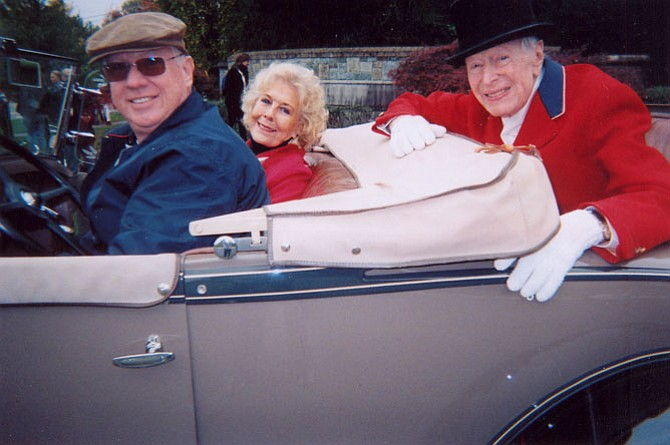 Seated in the rumble seat of a 1931 Model A Ford Roadster is Austin H. Kiplinger, the Grand Marshal of the 2015 Potomac Day Parade. Kiplinger, 97, is wearing Potomac Hunt formal hunting attire. He is a former hunt committee chairman and a member since 1961. Bonnie Nicholson, and car owner/driver, Chuck McDonald, are seated in front.