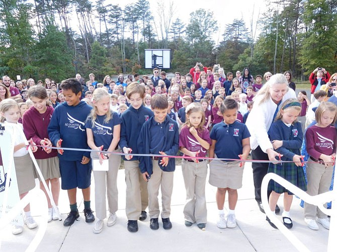 Ad Fontes students cut the ribbon on the new building with Lower School Office Manager Joan Druessel.