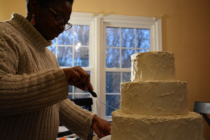 "TaMeisha Norris, owner of allergy-friendly bakery Out of the Bubble, frosts a ""dummy cake"" used for display in her Springfield dining room."