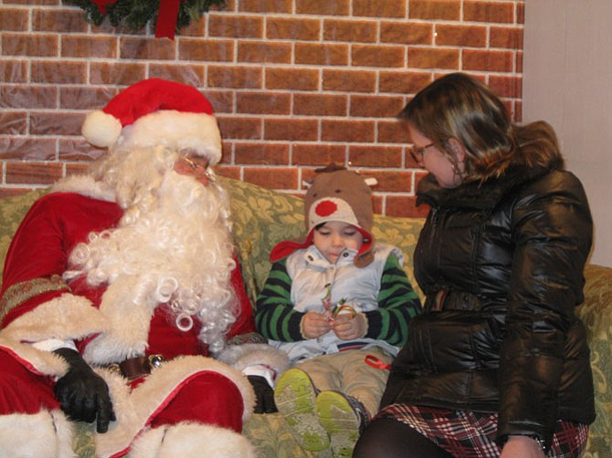Visiting with Santa are Jackson Whitt, 4 1/2, with his mom Cheryl of Great Falls.