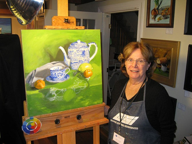 Fine artist Carol Howard, who works at Artists' Atelier in the Great Falls Village Center in Great Falls, with two of her recent pieces.