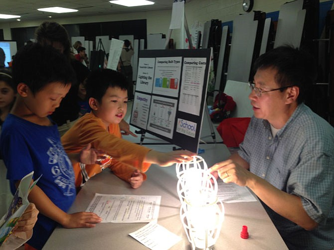 Forestville Parent and PTA co-vice president of Curriculum Niu‐Niu Chen of Great Falls volunteers at the event to help children observe and calculate the energy costs of three different kinds of bulbs.