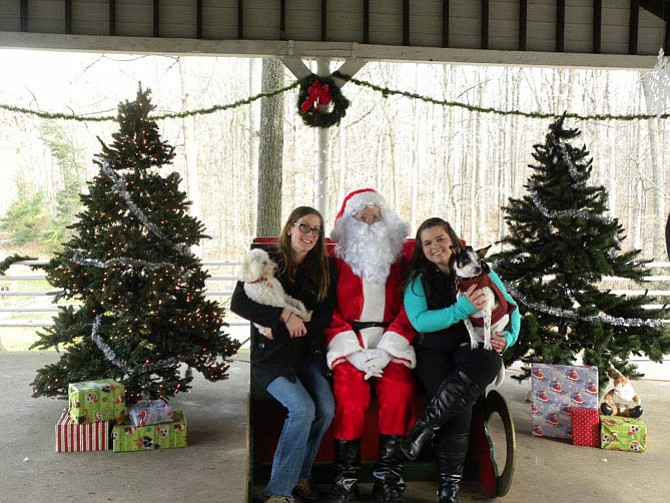 Katelynn Bradley, of Springfield, with pet Layla and Amanda Temenak, of Alexandria, with pet Romeo, flank Santa at the pavilion in Lake Accotink Park in Springfield.
