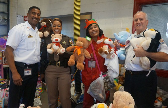Firefighters and Friends founder Capt. Willie Bailey, left, is joined by Charise Mitchell, Annie Dawkins and Fairfax County Fire Chief Richard Bowers at the Dec. 15 toy distribution day at Penn Daw Fire Station 11.