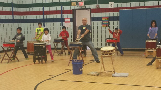 Instructor Mark Rooney, center, shows students how to play taiko. The opportunity was made possible through a grant from the Japan Foundation, which teachers at Fox Mill applied to back in June 2015. The afterschool session took place in late November 2015.