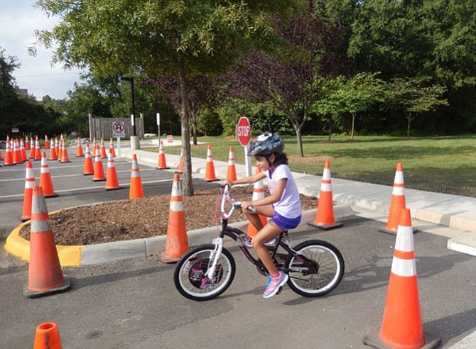 Liliana Silva, who attends St. Leo the Great Catholic School, bicycles through the safety-cone course at a Kids' Safety Day held by the City of Fairfax Police Department.