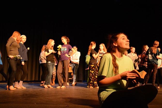 "Belle, played by senior Kirsten Chase (right), rehearses for ""Beauty and the Beast"" with the Village cast behind her."