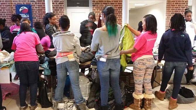 Middle and high school students from Northern Virginia and Maryland sort clothes by appropriate category.