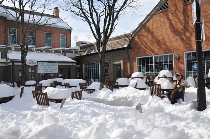 Doug Stevens enjoys some hot coffee in Potomac Village among the snow drifts.