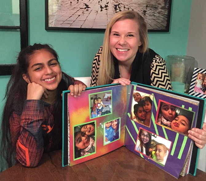 Hennesy (left) and her Community Lodgings mentor Dana Gilbertson display the scrapbook they worked on together last summer.