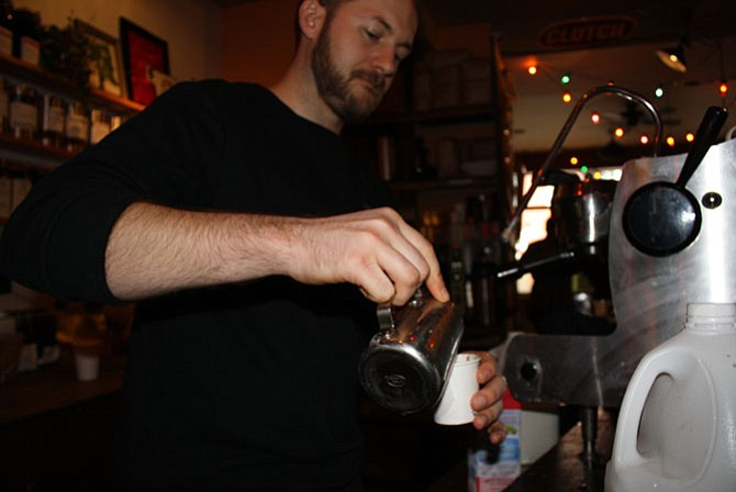 Cam Houghtaling steams a latte behind the bar.