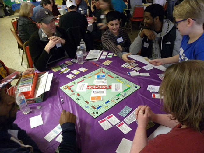 The players at this table during second round of the ninth Monopoly tournament wheel and deal to buy and sell property.