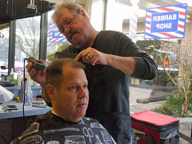 Brent McBurney follows Murphy into the barber chair. He has come to get a trim before his upcoming business trip to two human rights conferences in Thailand and Australia.