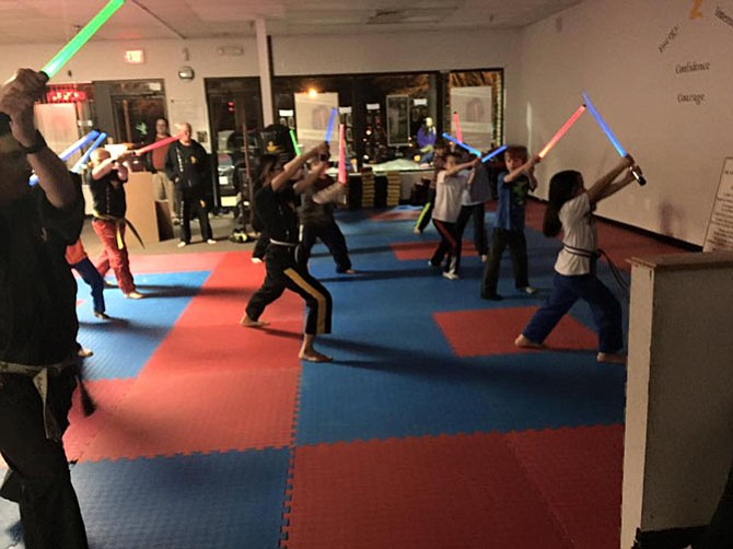 Students work on light saber skills during a class at Dietrich's Karate Fitness and Life Skills in Burke.