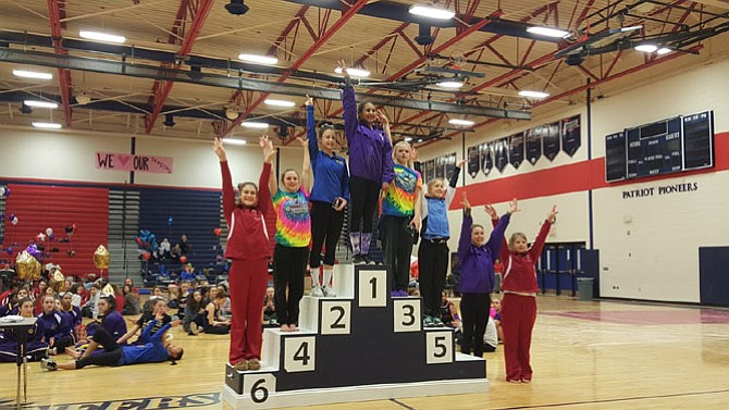 McLean gymnasts Carolyn Brown-Kaiser, far left, and Anna Brower, far right, finished sixth and seventh, respectively, on vault at the 6A North region meet on Feb. 13 at Patriot High School.