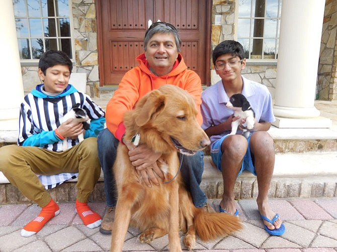 From left, Sachin Muralidhar, his father and brother Sid with foster Border Collies and Sparky (front).
