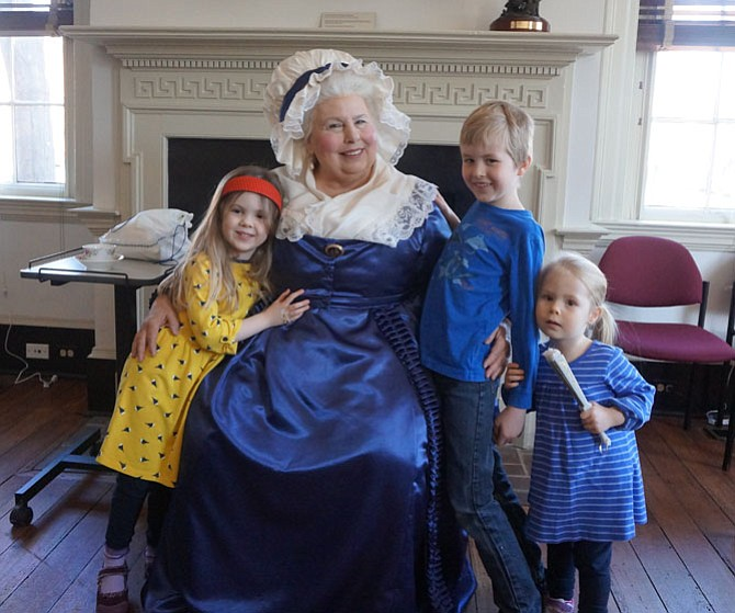 Mount Vernon character interpreter Mary Wiseman as Martha Washington poses with Eleanor Stoll, 3, and siblings Timothy, 8 and Margaret, 5, following a visit to Lloyd House Feb. 27 as part of the Talking With Washington series.
