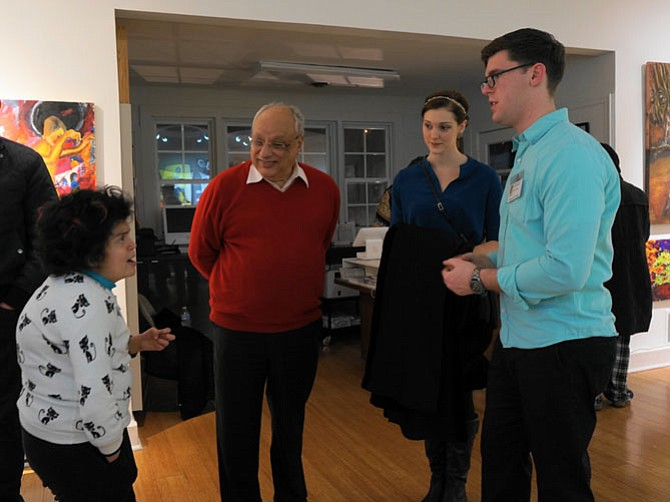 Exhibit curator Joshua Oliveira, right, talks with Yasmine Iskander about her work as Magdi Iskander and Tristann Brown look on.
