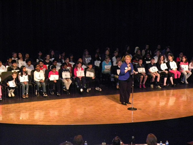 Debbie Kilpatrick, president of the Fairfax County Council of PTAs, thanks sponsors of the 10th Fairfax County Spelling Bee. Behind her are the 62 participants of the Bee.