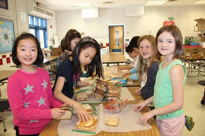 Churchill Road third graders Sophia Huang, Olivia Park, Ava Jackson and Avery Orfitelli formed a production line to make sandwiches for Martha's Table.