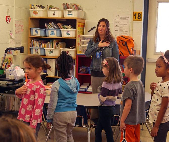 "Kate Martin joins the morning school program ""Good Morning the MacArthur Show"" in leading the pledge of allegiance for her kindergarten class on Wednesday morning."