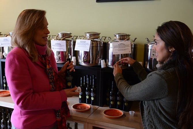 Patty Damiani of the Fort Hunt area (left) and Ransha Ahmed of Alexandria sample and discuss some of the flavored balsamic vinaigrettes at EVOO at Mamma's Market.