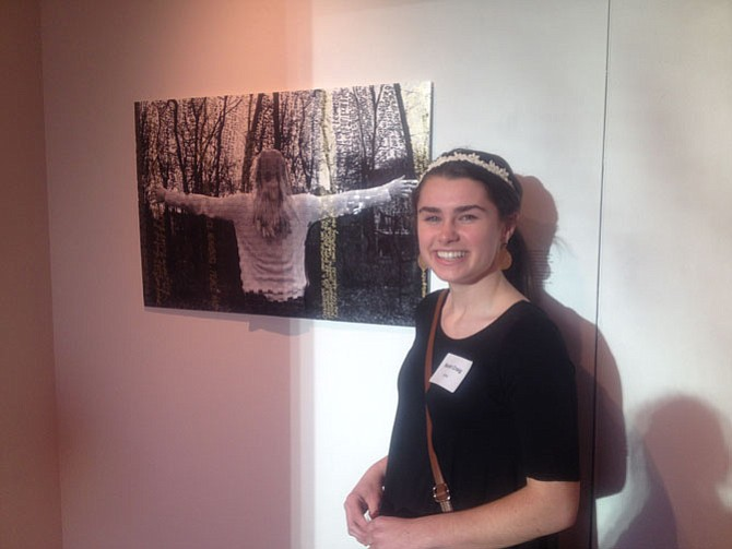 Sarah Craig, a senior at Oakton High School by her art piece on display at Greater Reston Arts Center (GRACE). Her mixed media piece includes commentary by local neighbors.