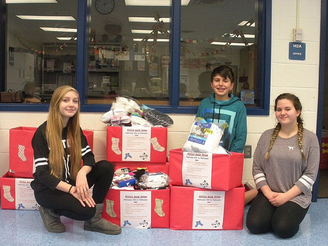 (From left) are Lanier students Jules Welch, Sami Saghir and Nora Farid with the boxes full of socks they collected.