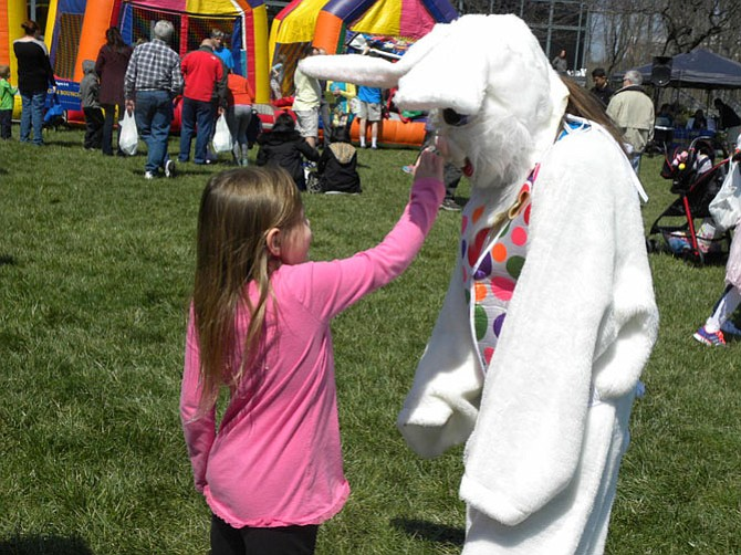 Haley MacLean, of Fairfax, inspects the Easter Bunny's nose.